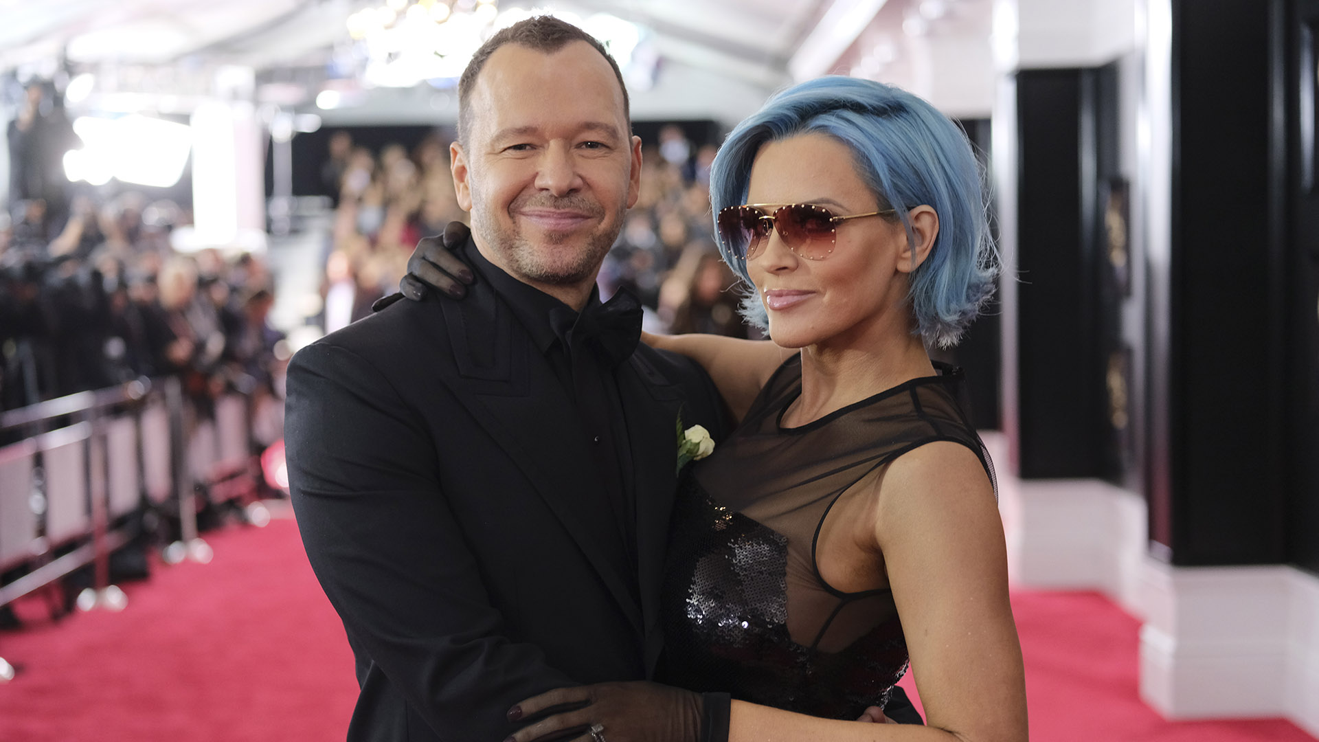 Blue Bloods star Donnie Wahlberg can't keep his hands off wife Jenny McCarthy, who debuts a new blue 'do on the red carpet.