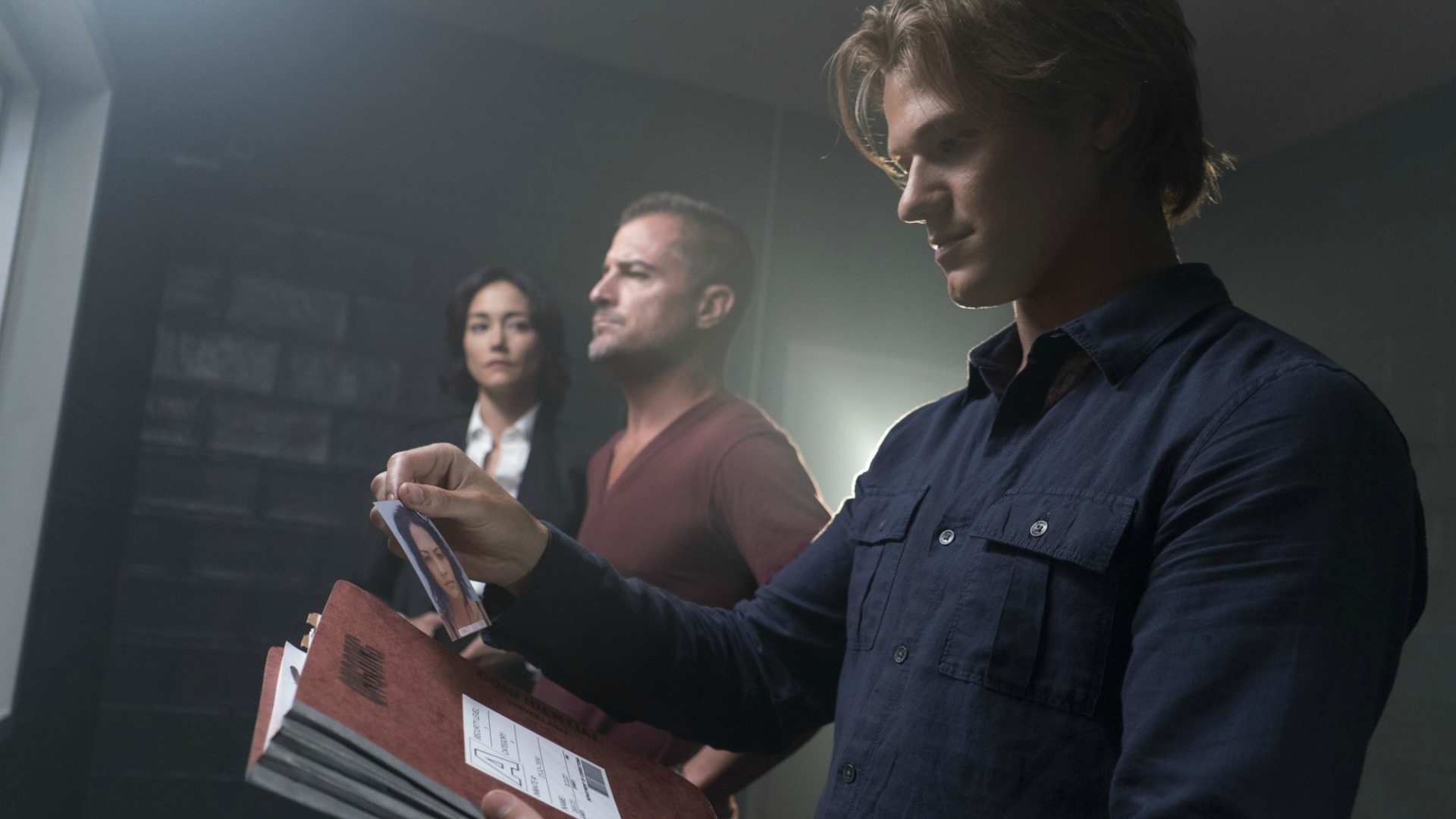 MacGyver reads through files.
