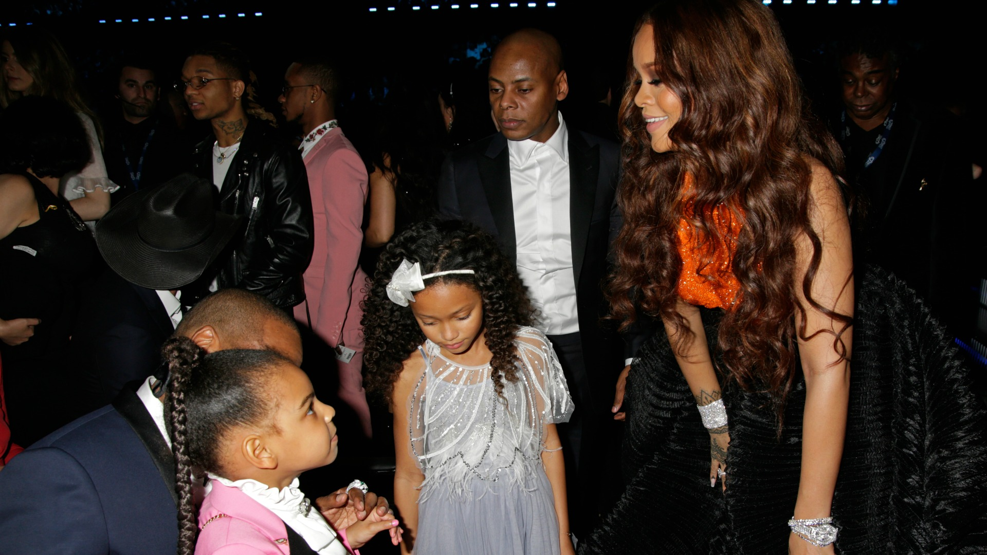 Rihanna smiles when she approaches Blue Ivy, who's to be sitting on the lap of her dad, Jay Z.