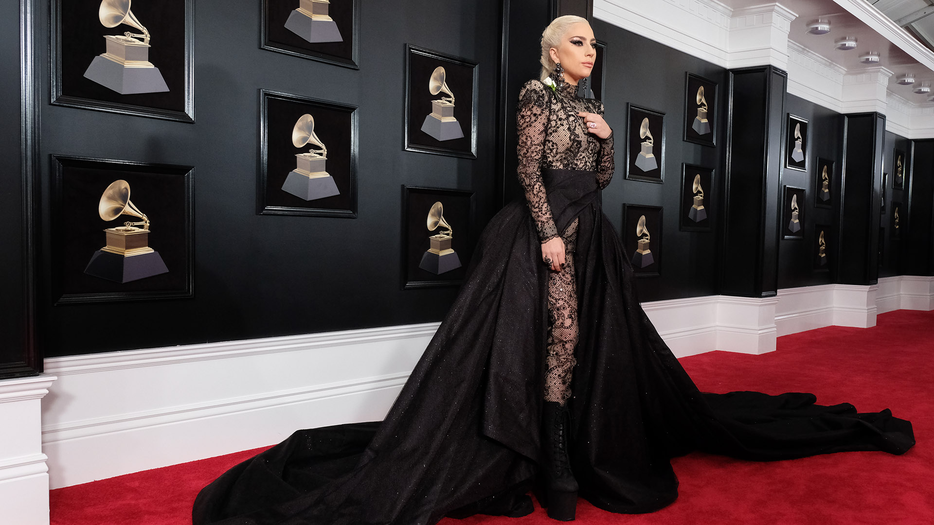 Lady Gaga pours herself onto the 60th Annual GRAMMY Awards red carpet in a black lace jumpsuit and long black train.