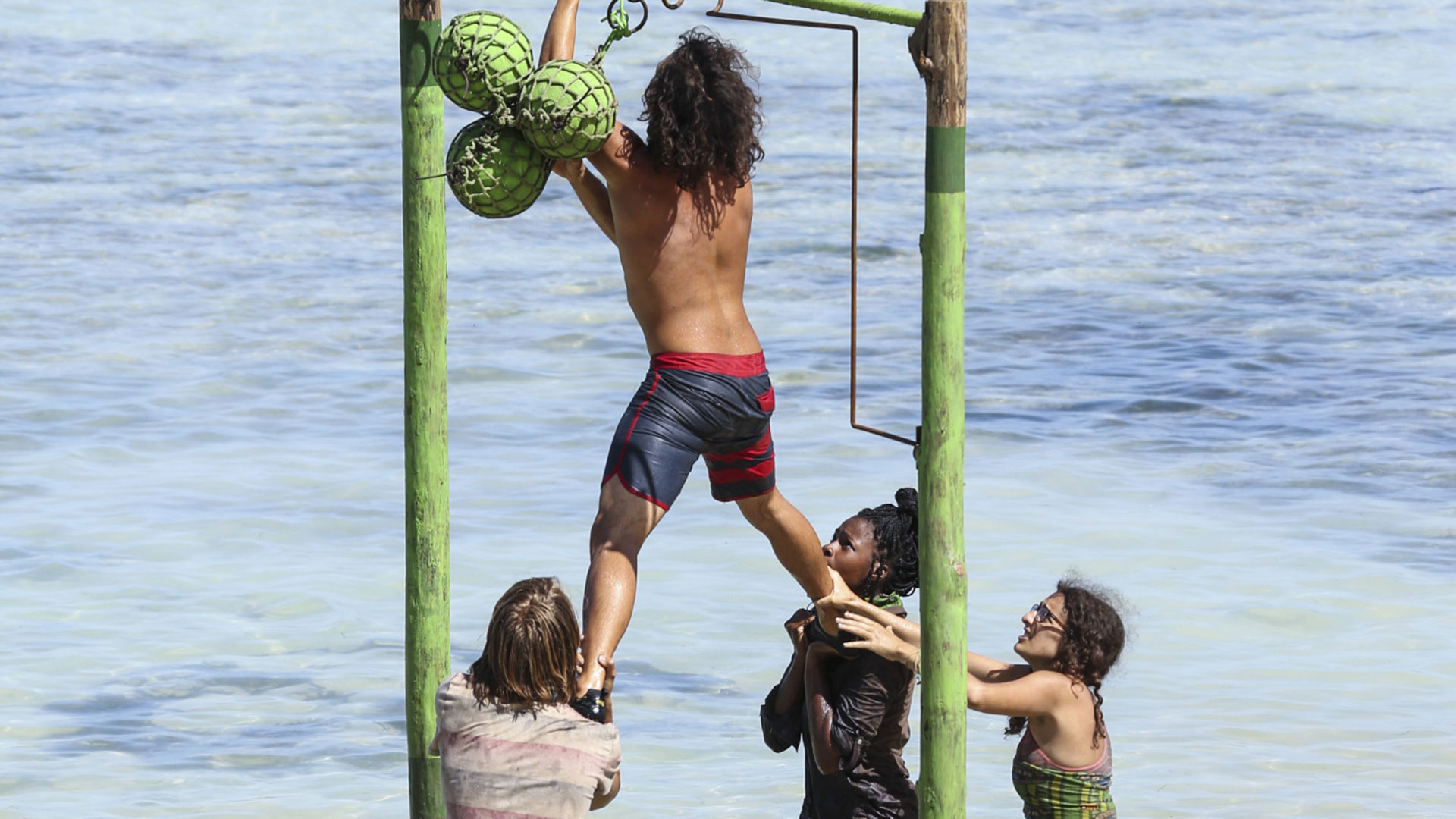Jay's tribe mates hold him up as he takes charge of the challenge.
