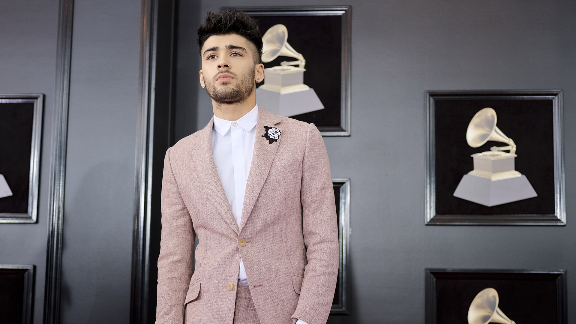 Zayn Malik stopped by to give his best model pose while wearing a pink suit accentuated with a white rose stitched on the lapel.