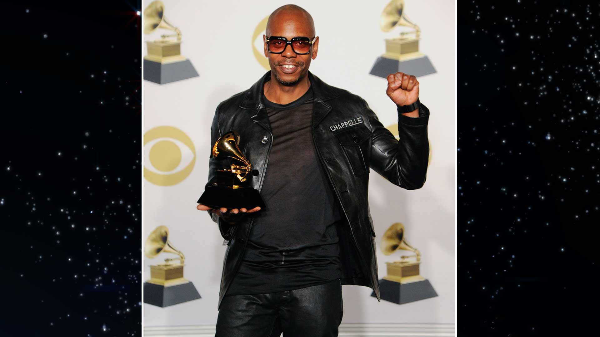 Comedian and Best Comedy Album winner Dave Chapelle throws a triumphant fist in the air.