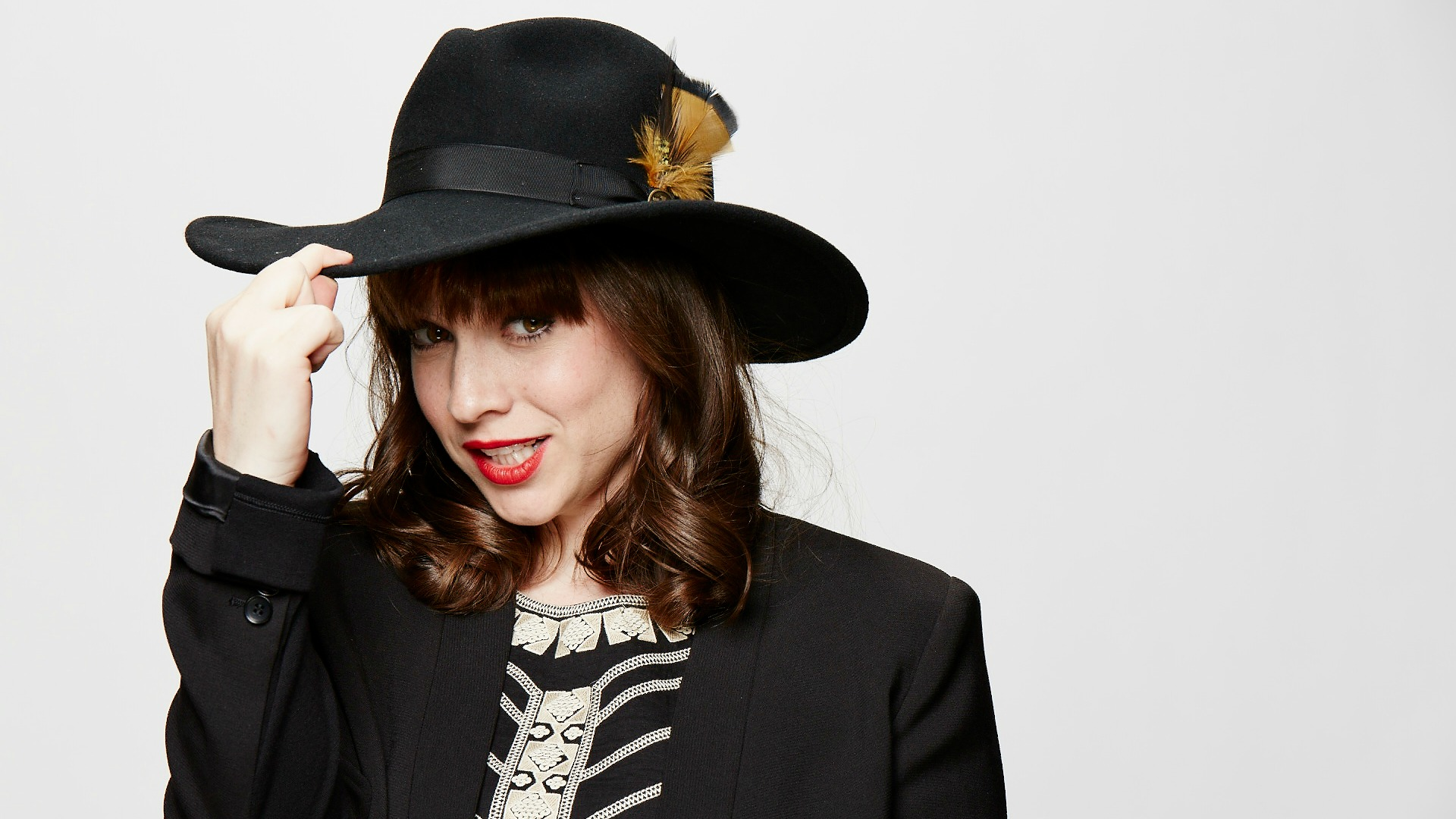 Renée Felice Smith tips her feather-adorned hat.