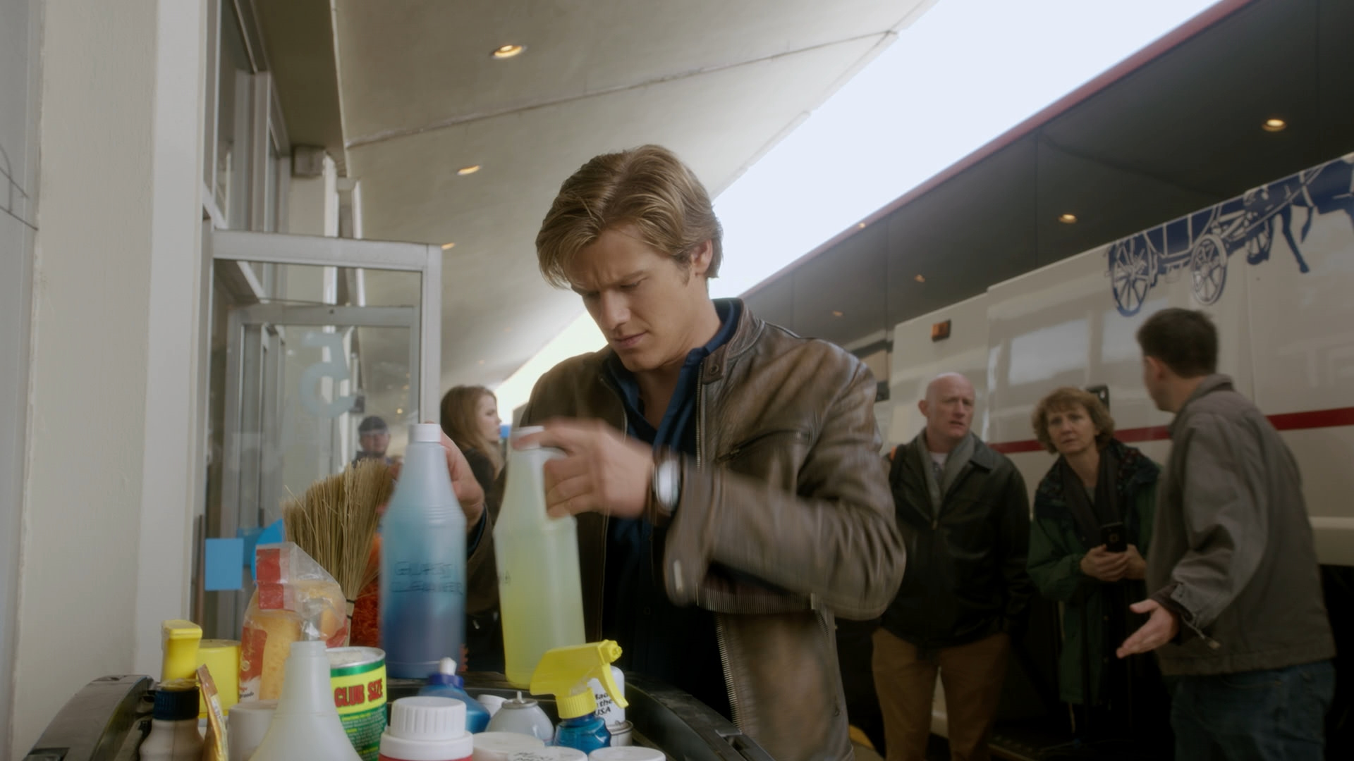 MacGyver rummages through cleaning products.