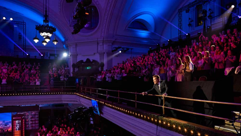 James Corden threatens to spit from the top balcony.