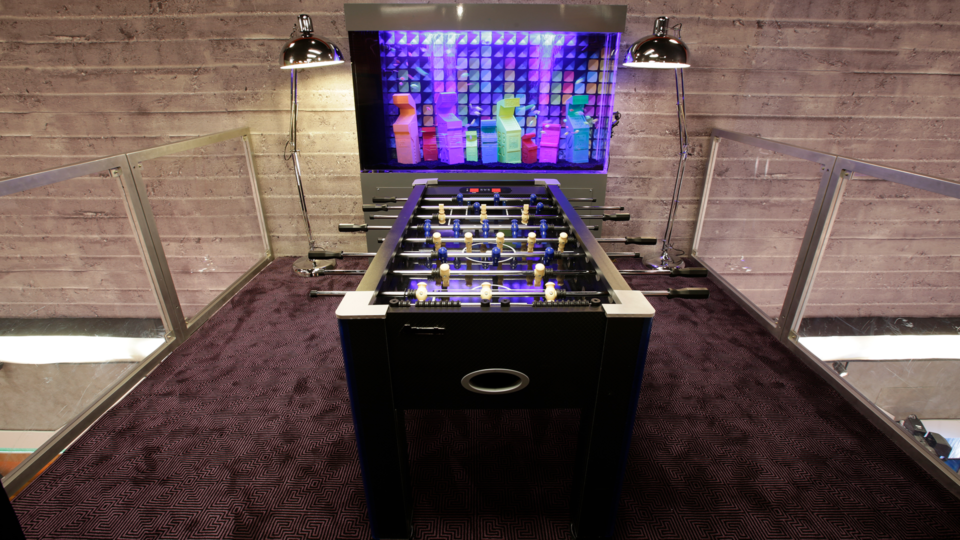 Upstairs, the bridge has been transformed into a gaming lounge with a classic foosball table and a giant aquarium with neon tropical hybrid fish swimming among sunken custom 3D printed miniature themed arcade games.