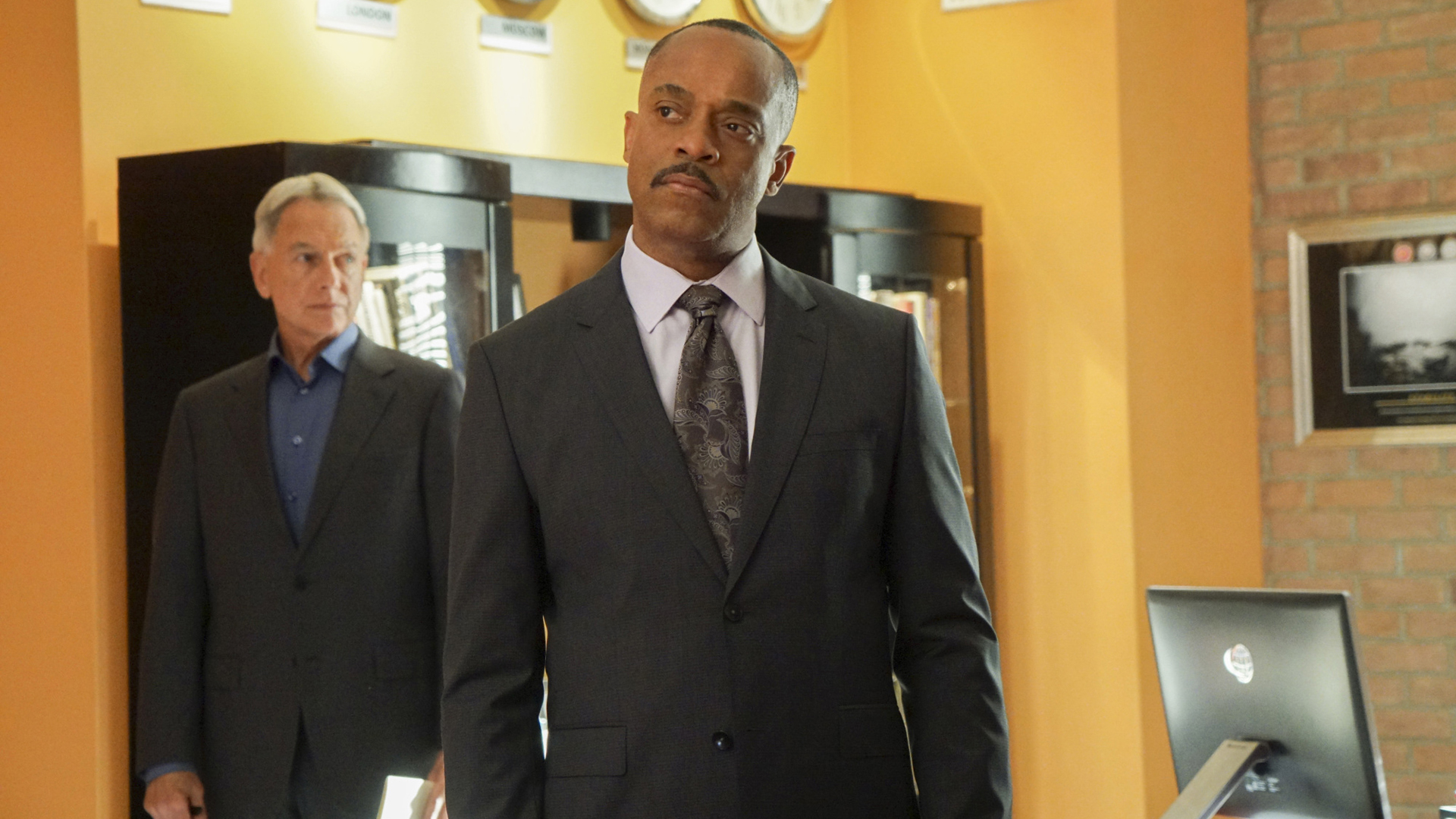 Vance, standing in front of Gibbs, absorbs the situation.