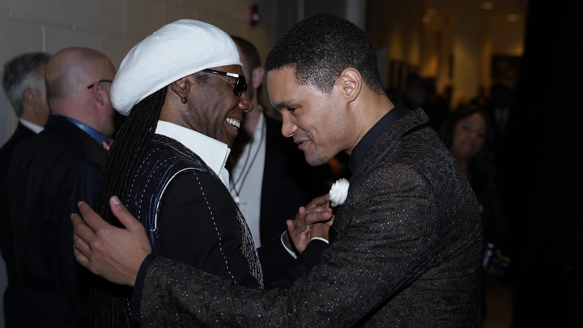 Comedian and GRAMMY presenter Trevor Noah gets a hug from funk legend Nile Rodgers.