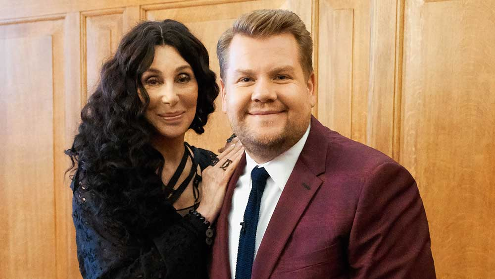 Cher tests the strength of James Corden's right shoulder.