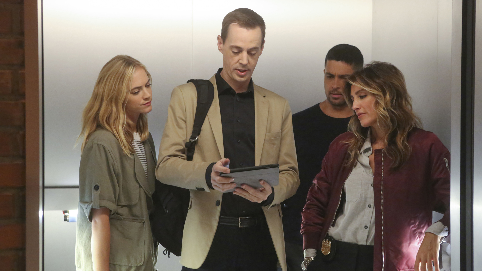 The team gathers to look at what's on McGee's tablet.