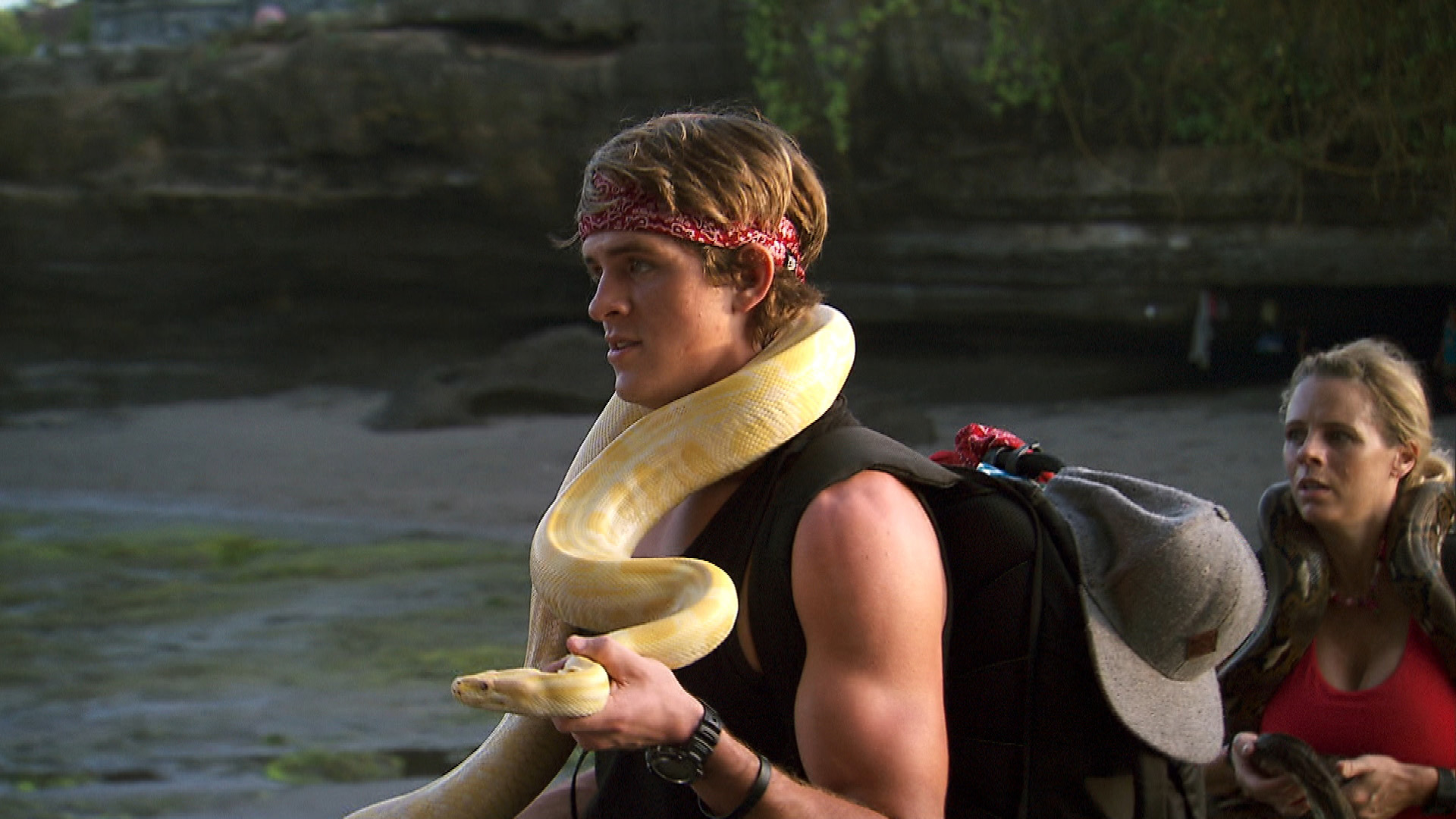 Cole carries a slithering snake in Bali.