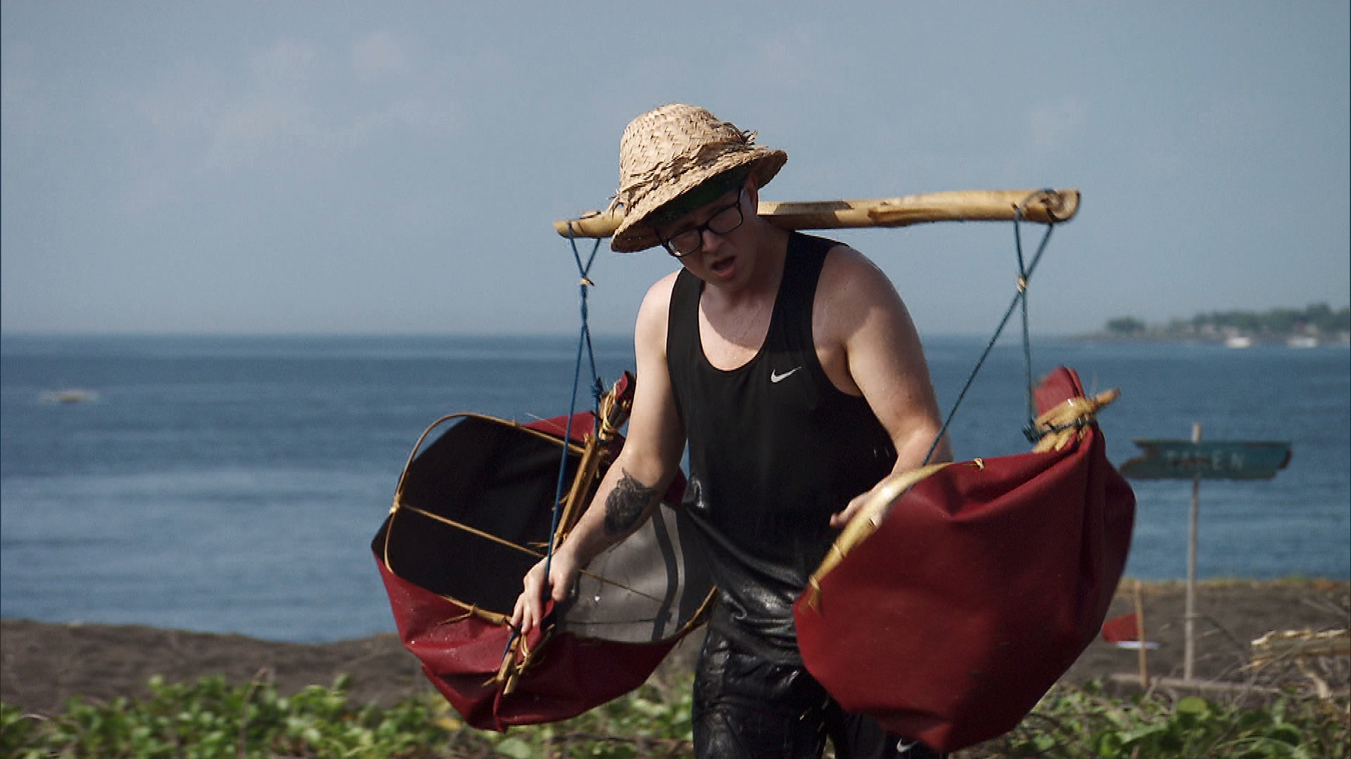 Tyler carries large loads of water from the sea to the sand.