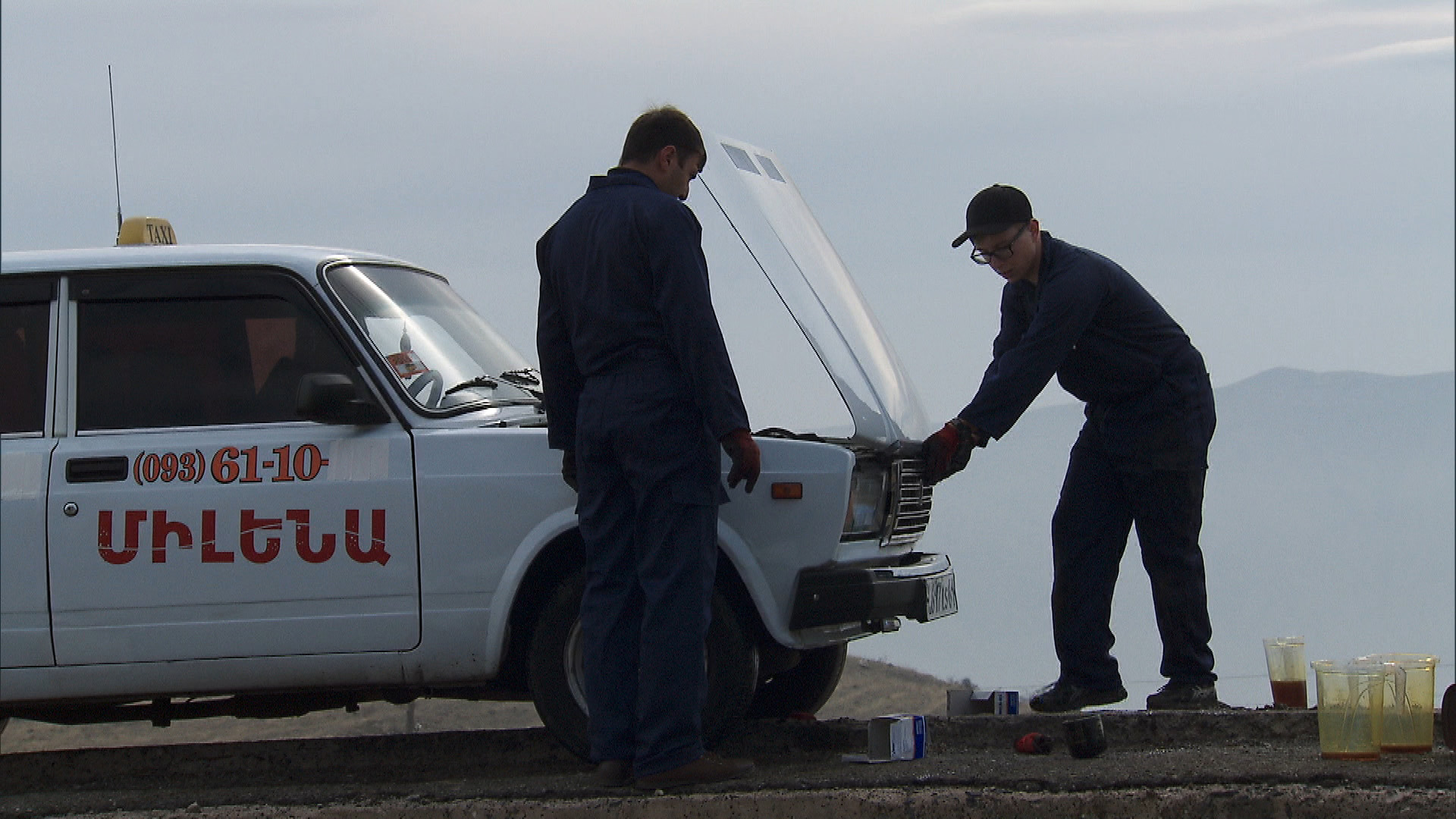In this Roadblock, Tyler (right) has to change the oil in a Lada taxi.